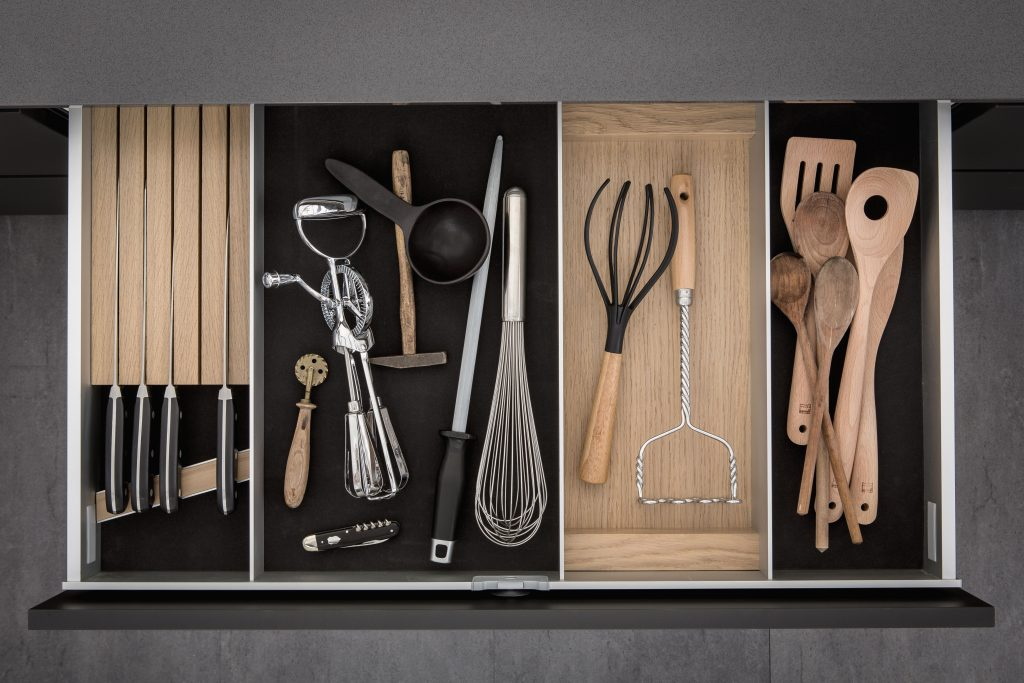 SieMatic - dark smoked cheshunt and light oak lining and moveable aluminium panels with utensils